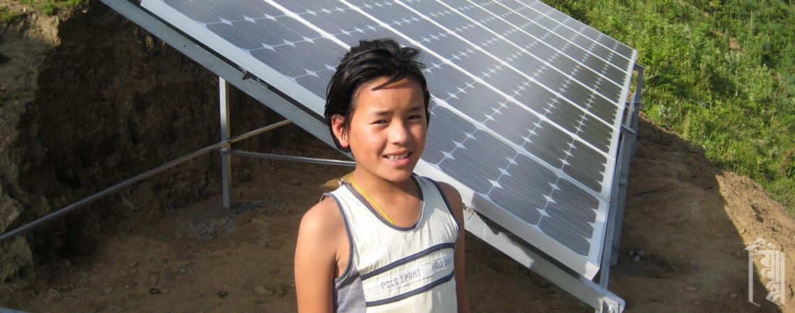 A Jhamtse Gatsal student stands next to the Community's first set of solar panels, installed in 2009.