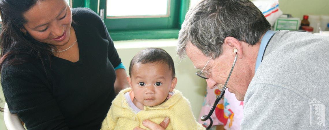 A young Community member gets a medical checkup from a visiting doctor.